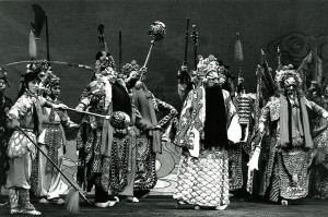 A black and white photograph of a scene from Peking Opera's production of 'Havoc in Heaven' entitled 'The King of Heaven's Armies' performed at Birmingham Hippodrome. The image shows numerous performers in traditional dress and wearing masks and headdresses. The opera was performed at the Hippodrome on 14 & 15 October 1986.